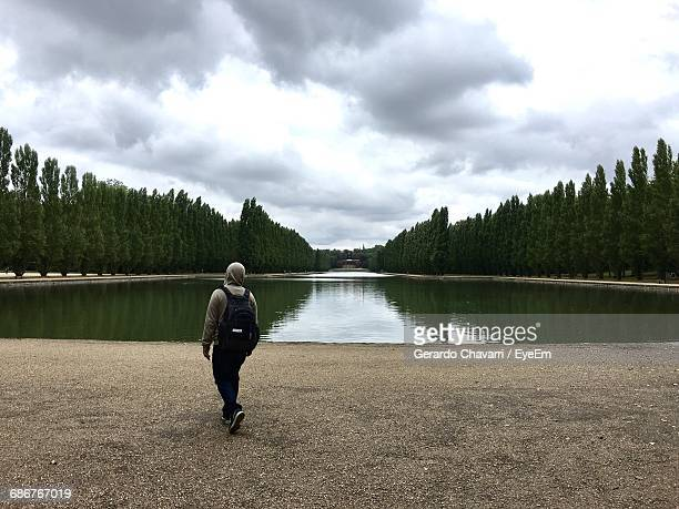 Rear View Of Man By Pond Amidst Trees At Parc De Sceaux Against Cloudy Sky