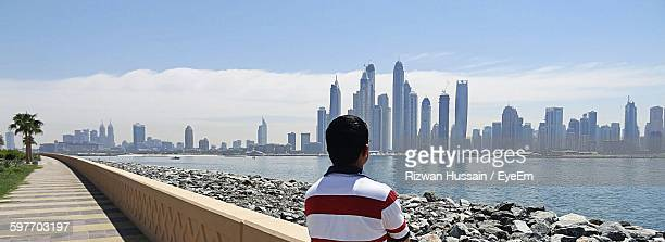 Rear View Of Man By River With Urban Skyline In Background Against Sky