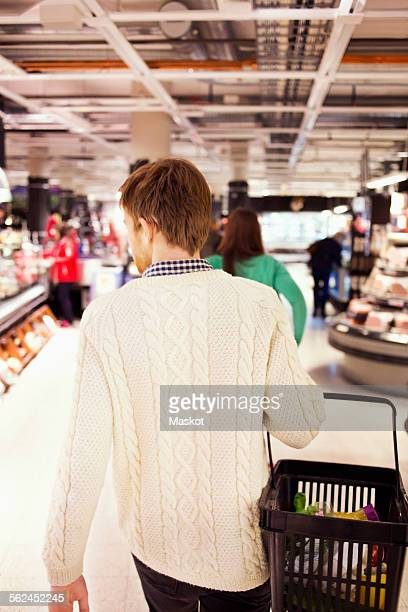Rear view of man carrying basket while walking at supermarket