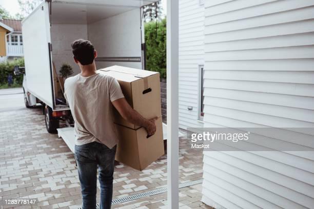 rear view of man carrying cardboard boxes towards van - movilidad fotografías e imágenes de stock