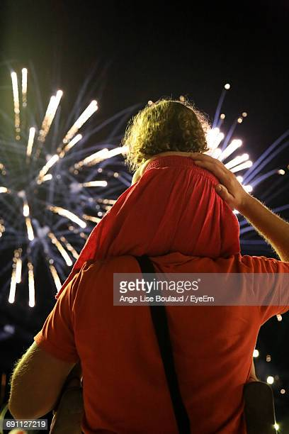 Rear View Of Man Carrying Daughter On Shoulder While Looking At Firework Display