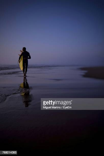 Rear View Of Man Carrying Surfboard While Walking At Beach During Dusk