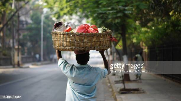 Rear View Of Man Carrying Vegetables In Basket On Street