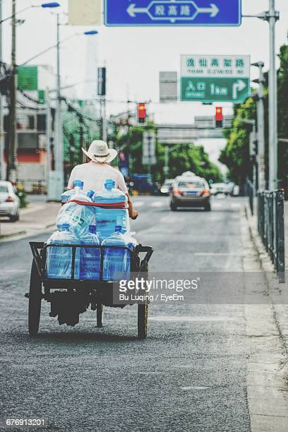 Rear View Of Man Carrying Water Bottles On Vehicle At Street
