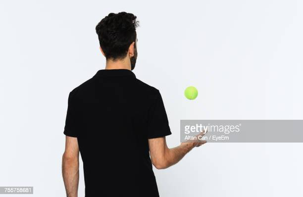Rear View Of Man Catching Tennis Ball Against White Background