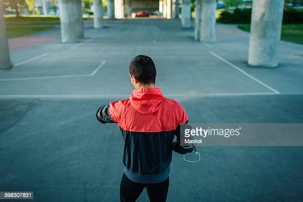 Rear view of man checking time while standing on street