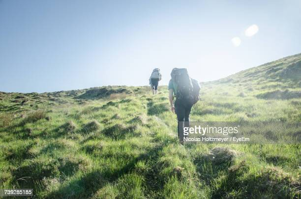 rear view of man climbing mountain against sky - camping stock photos and pictures