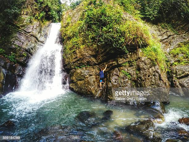 Rear View Of Man Climbing On Rock Formation By Waterfall