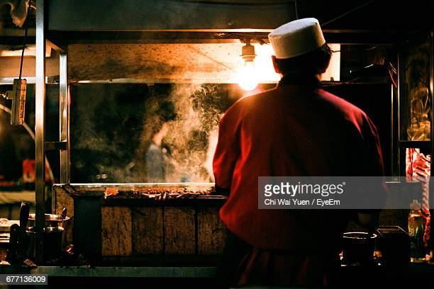 Rear View Of Man Cooking Food At Market Stall