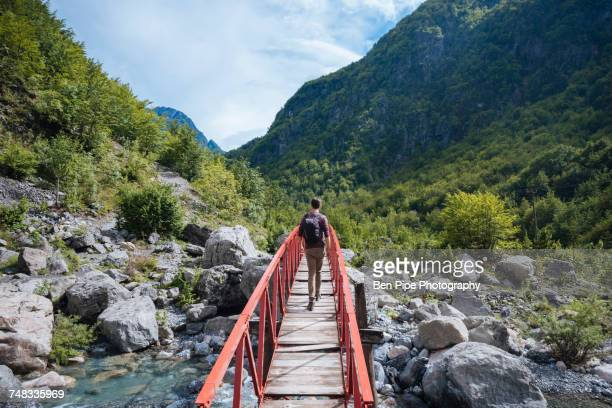 rear view of man crossing bridge, accursed mountains, theth, shkoder, albania, europe - albania stock-fotos und bilder