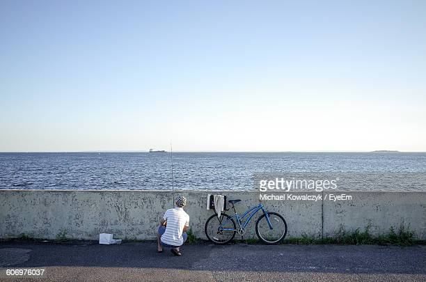 rear view of man crouching against retaining wall at seaside - retaining wall stock pictures, royalty-free photos & images