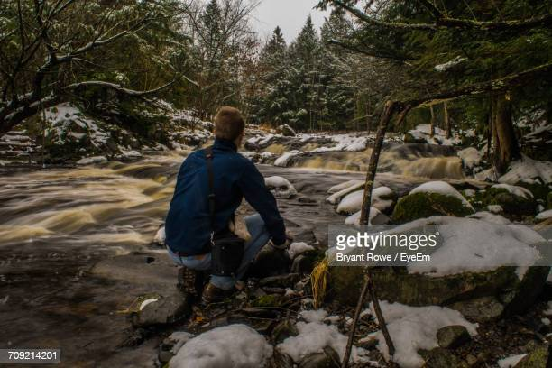Rear View Of Man Crouching By River In Forest During Winter