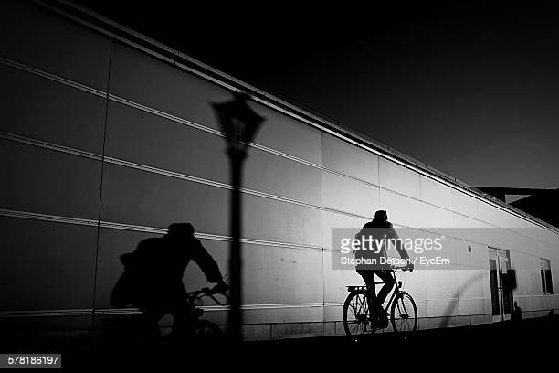 Rear View Of Man Cycling By Building At Night
