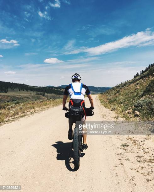 Rear View Of Man Cycling On Dirt Road Against Sky