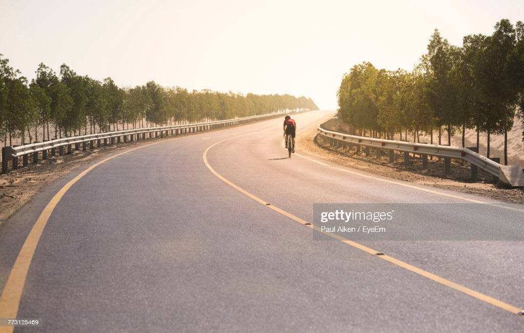 Rear View Of Man Cycling On Road Against Clear Sky : Photo