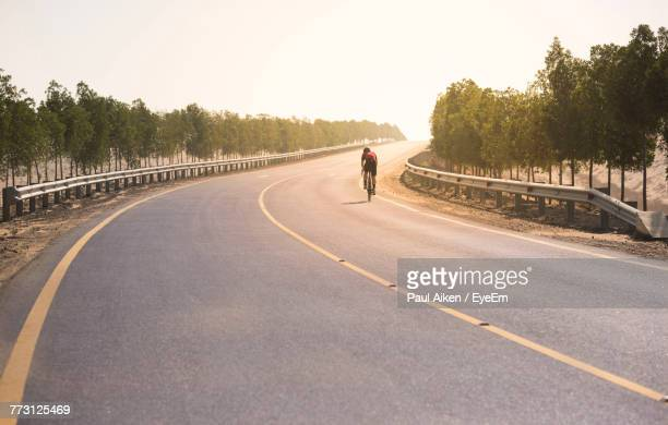 rear view of man cycling on road against clear sky - aikāne stock pictures, royalty-free photos & images