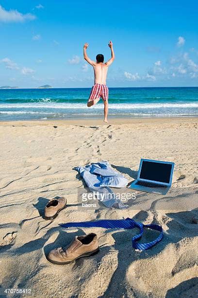 Rear view of man ditching his work attire and running to sea
