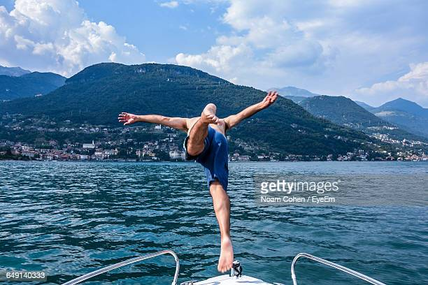 Rear View Of Man Diving Into Lake Como From Boat Against Mountains