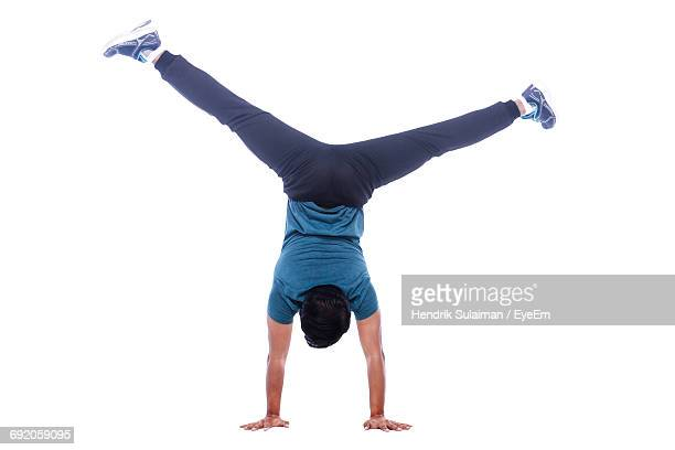 rear view of man doing hand stand against white background - benen gespreid stockfoto's en -beelden