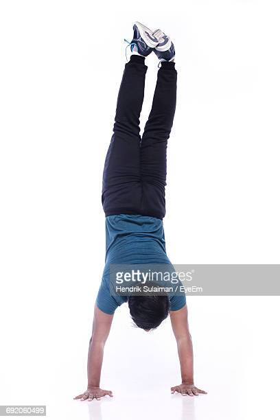 Rear View Of Man Doing Hand Stand Against White Background