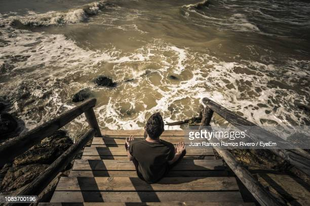 Rear View Of Man Doing Yoga On Steps Against Sea