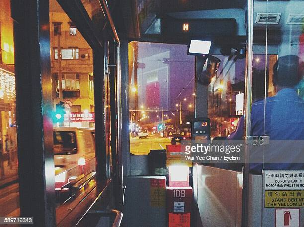 Rear View Of Man Driving Bus On Illuminated Street