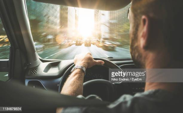 rear view of man driving car on street in city - steering wheel stock pictures, royalty-free photos & images