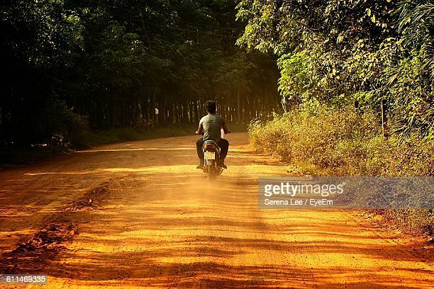 Rear View Of Man Driving Motorcycle On Dirt Road