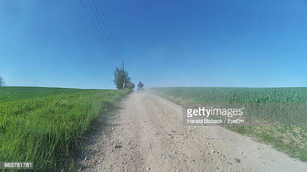 Rear View Of Man Driving Quadbike On Dirt Road Amidst Grassy Field Against Clear Blue Sky