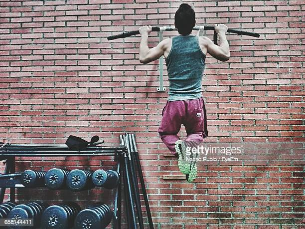 rear view of man exercising in gym - chin ups stock photos and pictures
