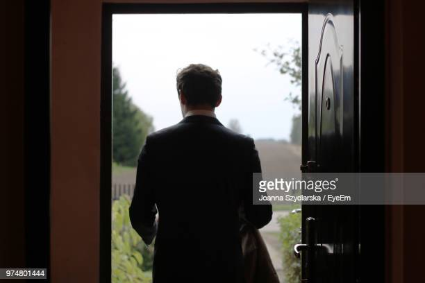 rear view of man exiting house - leaving photos et images de collection