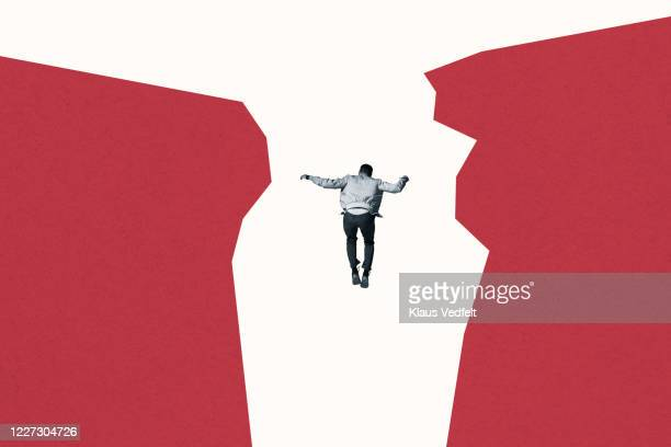 rear view of man falling between red cliff - graphic accident photos stock pictures, royalty-free photos & images