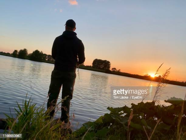 rear view of man fishing against clear sky during sunset - オランダ リンブルフ州 ストックフォトと画像