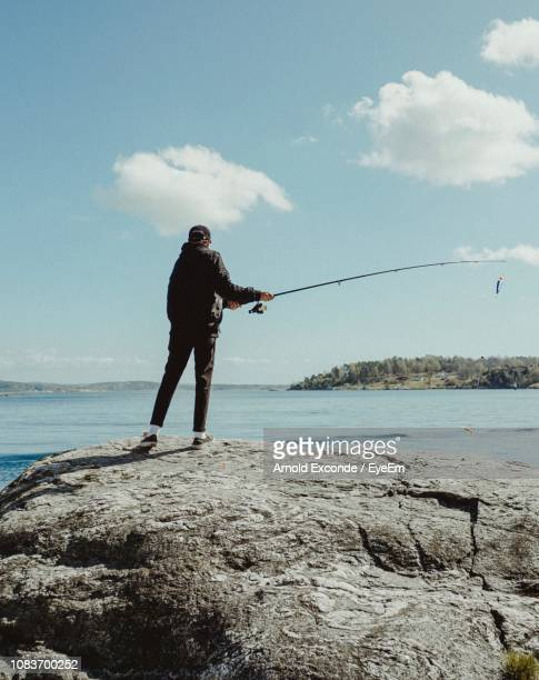 rear view of man fishing at beach against sky - 沿岸 ストックフォトと画像