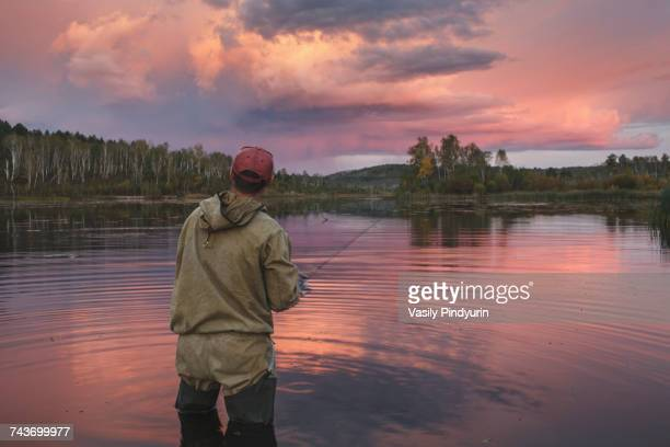 Rear view of man fishing in lake against cloudy sky at forest during sunset, Svobodniy, Amur, Russia