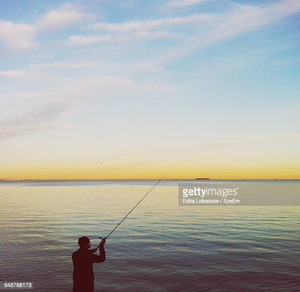Rear View Of Man Fishing In Lake Against Sky