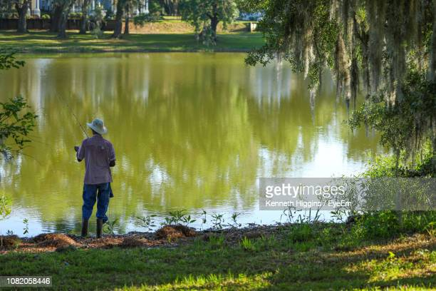 rear view of man fishing in lake - tallahassee stock pictures, royalty-free photos & images