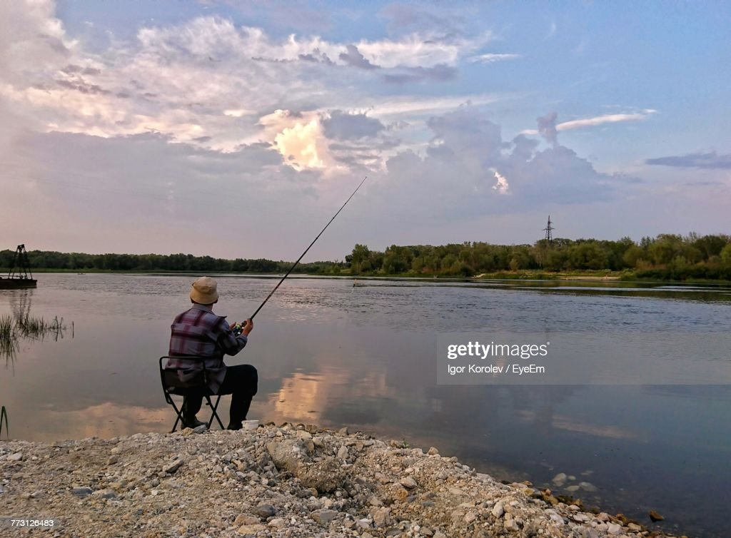 Rear View Of Man Fishing In Lake While Sitting Against Sky During Sunset : Photo
