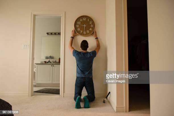 rear view of man fixing clock on wall at home - mid adult men stock pictures, royalty-free photos & images