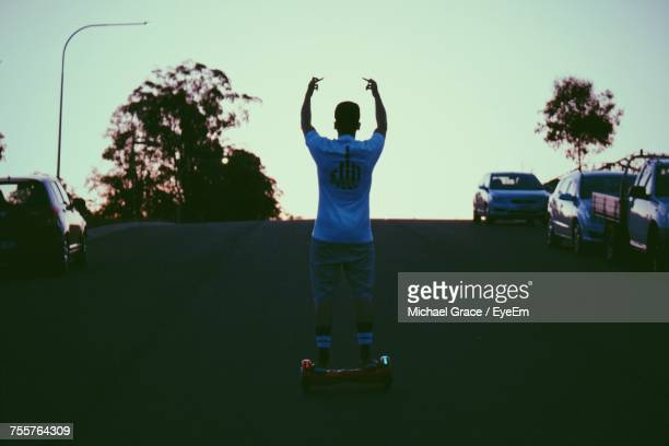 Rear View Of Man Gesturing While Standing At Segway On Road