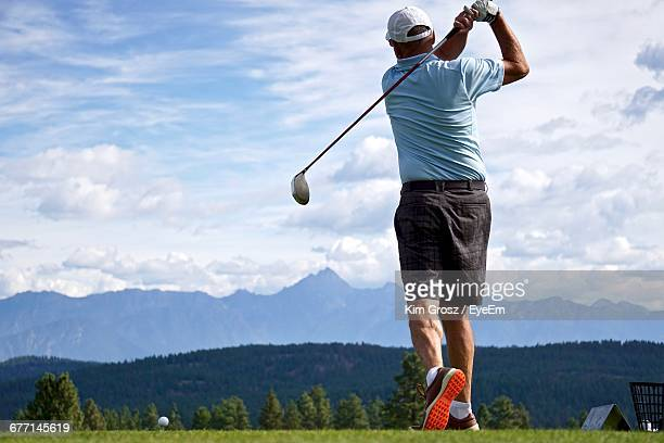 Rear View Of Man Golfing On A Golf Course In The Canadian Rockies