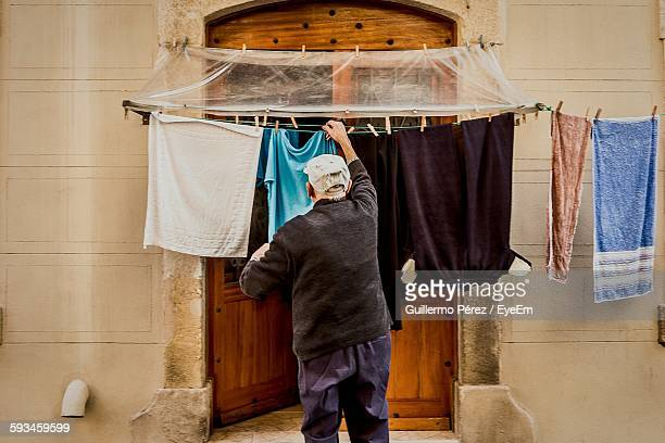 Rear View Of Man Hanging Laundry On Clothesline