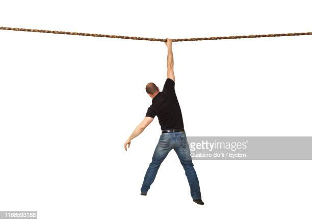 rear view of man hanging on rope against white background - hanging stock pictures, royalty-free photos & images