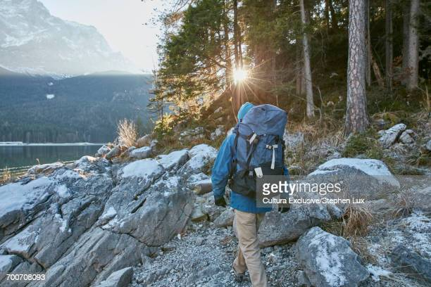 Rear view of man hiking by Lake Eibsee in winter, Zugspitze, Bavaria, Germany