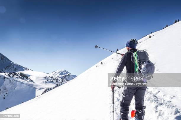 Rear View Of Man Hiking On Snowcapped Mountain Against Sky