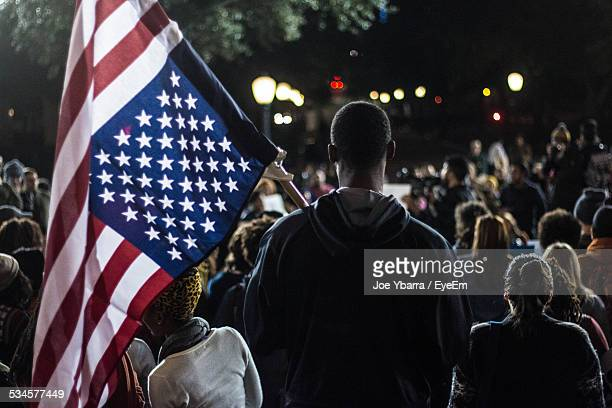rear view of man holding american flag in crowd - march stock-fotos und bilder