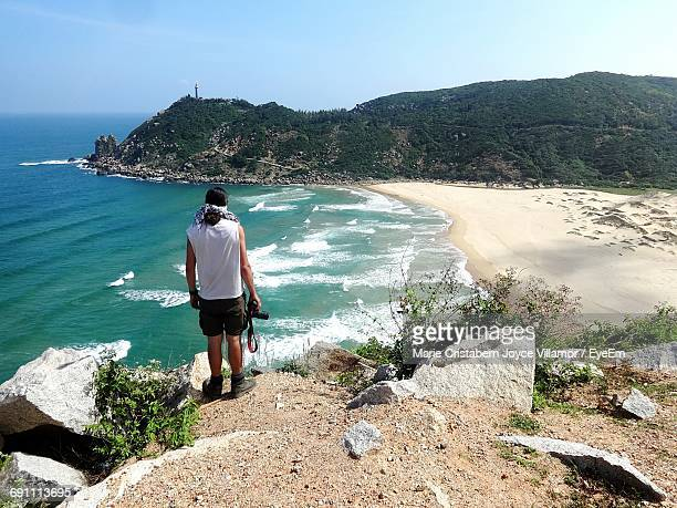 rear view of man holding camera while standing on rock overlooking beach - 見渡す ストックフォトと画像