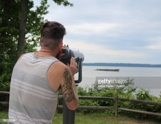 Rear View Of Man Holding Cigarette While Standing By Coin-Operated Binoculars Against Lake And Sky