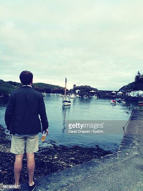 rear view of man holding drink standing at harbor - chauvin stock pictures, royalty-free photos & images