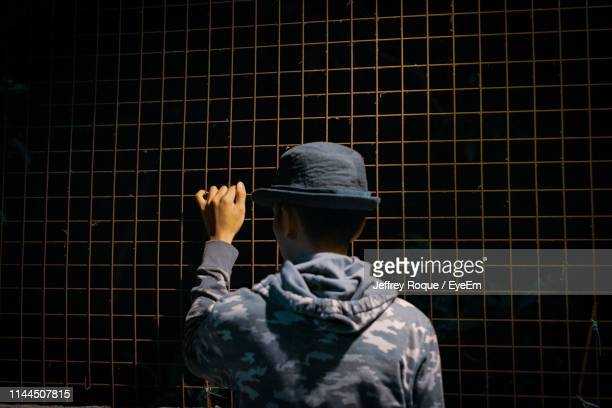 rear view of man holding fence - jeffrey roque stock photos and pictures